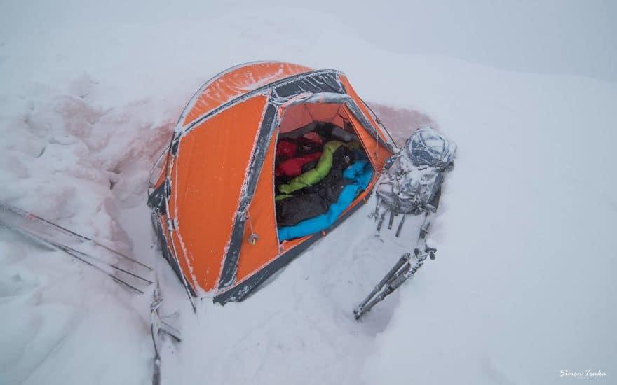 Окопана в снега палатка високо в планината през зимата.