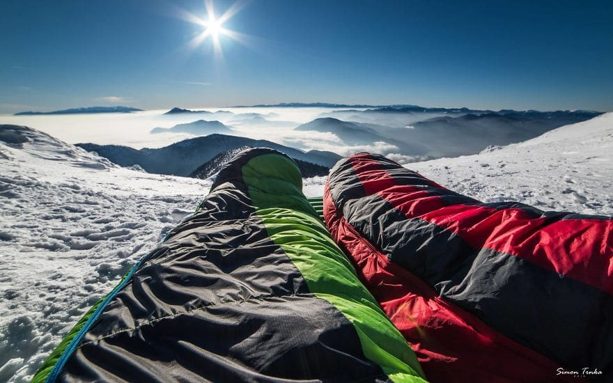 Посрещане на утринта в спален чувал високо в планината през зимата.